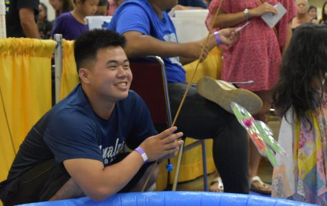 Senior Trent Nakata demonstrates proper fishing to children playing games at the Okinawan Festival.