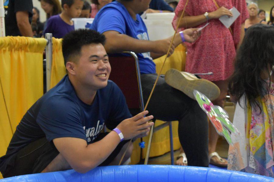 Senior Trent Nakata demonstrates proper fishing to children playing games at the Okinawan Festival.