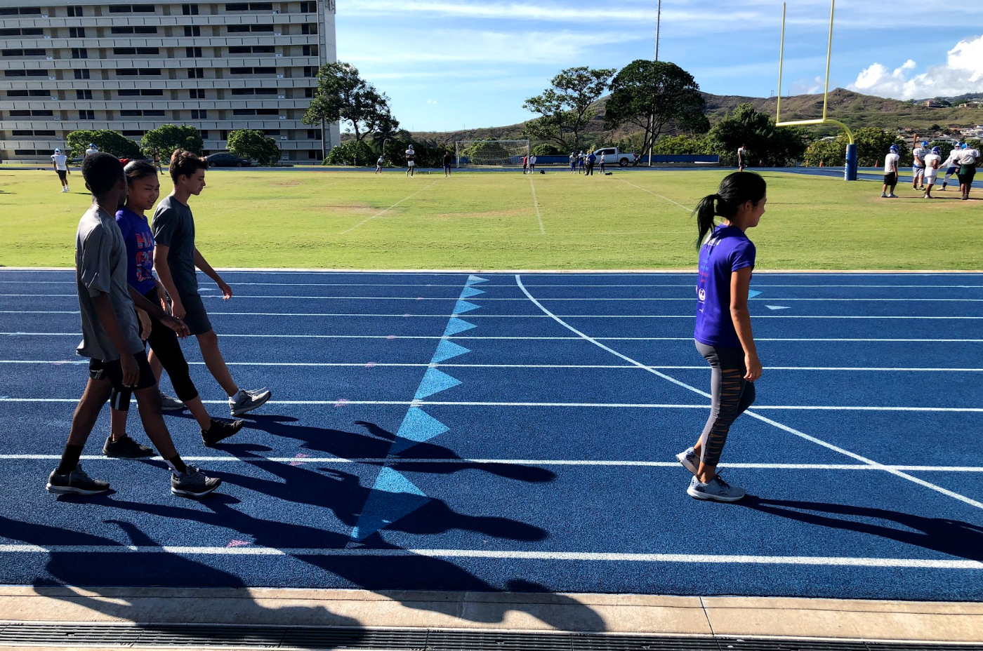 The Cross Country team warms up on the track field with the sun shining.
